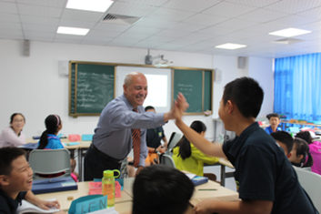 male teacher giving student high five in classroom
